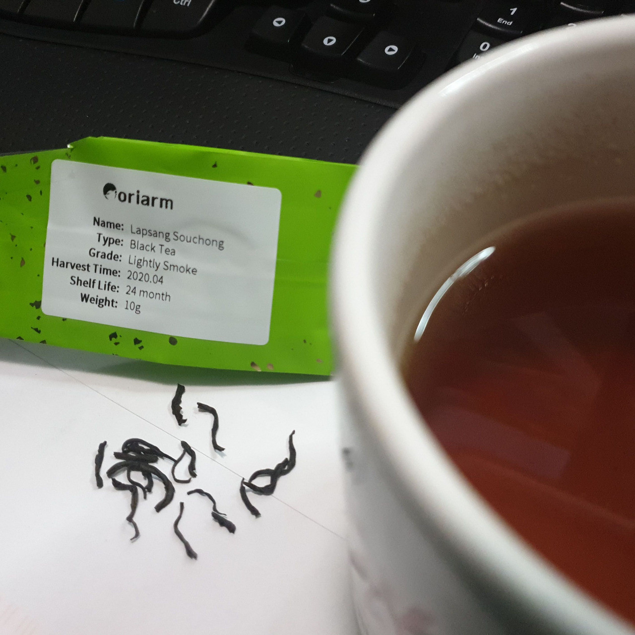 Lapsang Souchong black tea package with tea leaves next to it and a partially visible cup of brewed tea.